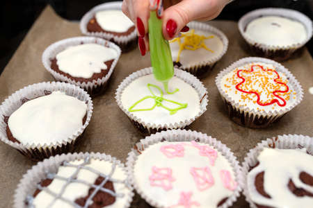 A woman squeezes colored frosting from a tube onto chocolate brown cupcakes covered with white frosting with colorful decorations.