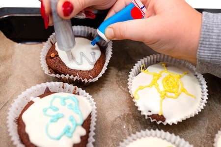 A child squeezes colored frosting from a tube onto chocolate brown cupcakes covered with white frosting with colorful decorations. Zdjęcie Seryjne