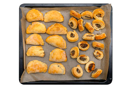 Frozen baked patties and dumplings in dough on a baking sheet on baking paper, isolated on a white background with a clipping path, top view.