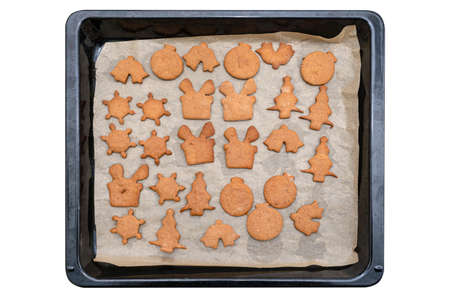 Baked gingerbread cookies in various shapes without decorations, lying on baking paper, isolated on white background witha a clipping path, top view.