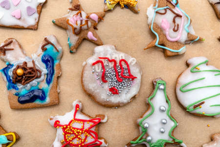 Hand decorated baked gingerbreads of various shapes, arranged on baking paper, top view. 版權商用圖片