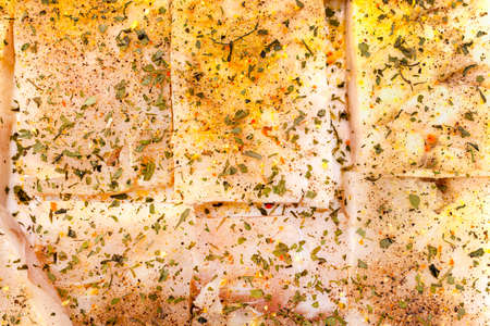 Background made of cod fish fillet cut into squares and sprinkled with spices, top view.