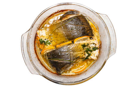 Baked pieces of carp in a glass bowl with melted butter, parsley and lemon slices, isolated on a white background , top view.