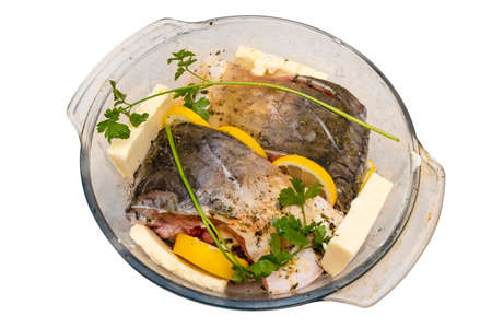Pieces of raw carp arranged in a glass bowl with butter, parsley and lemon slices, isolated on a white background, top view.