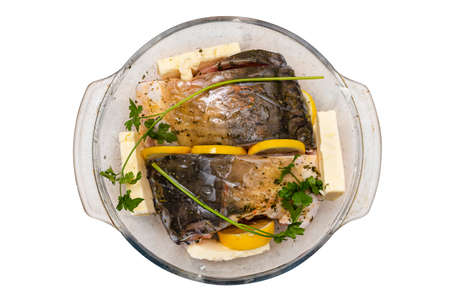 Pieces of raw carp arranged in a glass bowl with butter, parsley and lemon slices, isolated on a white background with, top view.