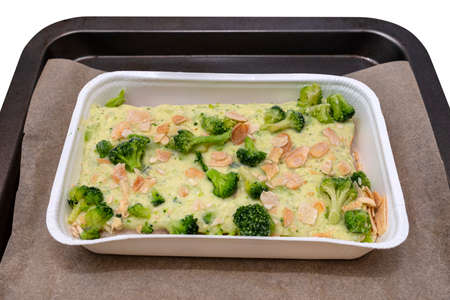 Frozen pollock fillet with broccoli and roasted almonds in a cream sauce lying on baking paper, isolated on a white background.