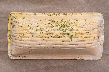 Frozen puff pastry with salmon lying on baking paper, isolated on a brown background top view.