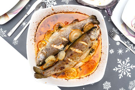 Baked two pieces of trout on a plate with onions and lemon slices dipped in oil on the holiday table, isolated