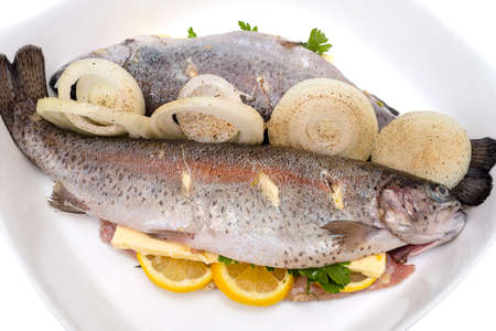 Fresh, raw two trout lying on a plate, stuffed with butter, onion, parsley and lemon slices, isolated on a white background