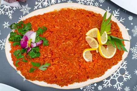 Baked fish fillets in carrot salad decorated with various vegetables on a decorative table, top view.
