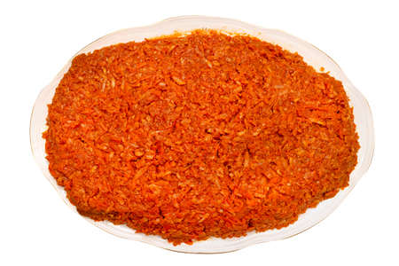 Baked fish fillets in carrot salad without additives on a decorative plate, isolated on a white background