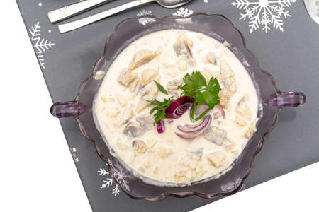 Raw herring in cream, standing in a glass vase on a holiday table in Poland, isolated on a white background 版權商用圖片