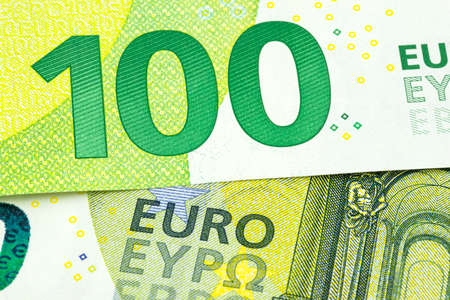 Macro shot of a European Union banknote of 100 EUR, close-up of the number one hundred, selective focus.