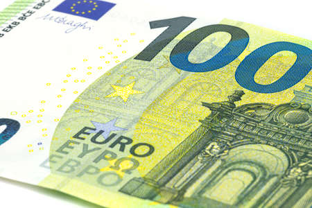 Macro shot of a European Union banknote of 100 EUR, close-up of the number one hundred, isolated on a white background, selective focus.