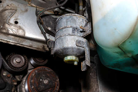 Worn fuel filter mounted and screwed on the car in the wheel arch. 版權商用圖片