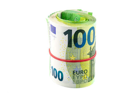 Macro shot of the European Union 100 EURO banknote, rolled up into a rubber band, isolated on a white background.