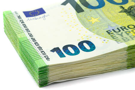 Macro shot of the European Union 100 EURO banknote, stack of banknotes lying on top of each other, isolated on a white background.