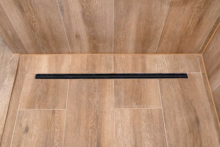 Modern black linear drain in a bathroom lined with ceramic tiles imitating wood.