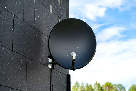 Black satellite dish mounted to the facade of the house, which is covered with black Foto de archivo