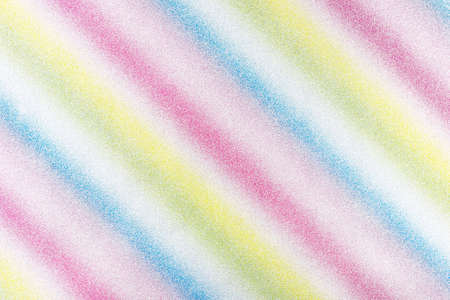 Background covered with glitter in diagonal lines in different colors of the rainbow, top view.