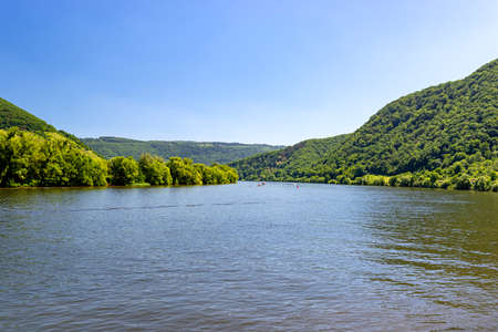 Beautiful view of a river flowing between grape and trees hills in western Germany, boats visible in the distance.