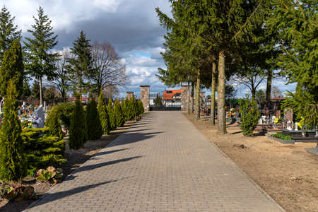 A paved alley that leads between the rows of tombs into a small cemetery with trees in the countryside on a sunny day with a cloudy sky. Stockfoto