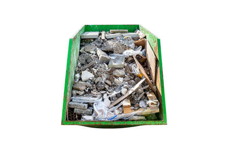 Large metal green container filled with rubble and construction waste, isolated on white background with a clipping path.