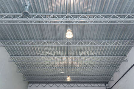Two light bulbs hanging from the ceiling under a metal lattice in a large industrial warehouse. Stockfoto