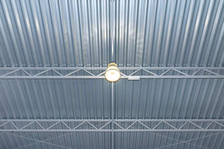 One bulb hanging from the ceiling under a metal lattice in a large industrial warehouse.