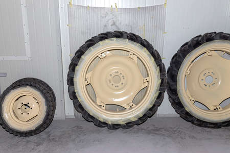 Freshly painted rims in a light color from a farm tractor standing in the hall.