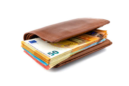 Brown leather mens wallet with a stack of Euro banknotes inside, isolated on a white background, 50 euros visible. Stockfoto