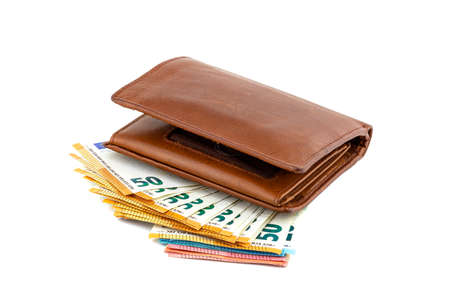 Mens brown leather wallet lying on a pile of Euro notes, isolated on a white background, visible 50 Euro.