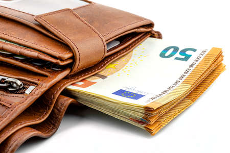 A macro shot of a brown mens leather wallet with a stack of Euro banknotes inside, isolated on a white background, visible 50 Euro. Stockfoto