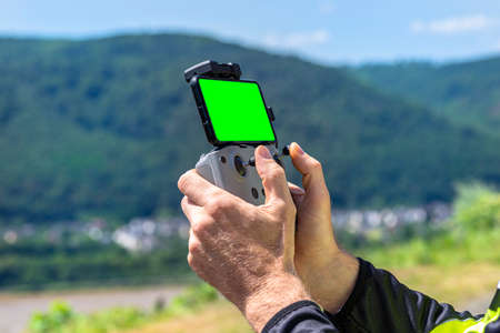 The man is holding a drone remote control with a green screen smartphone connected to it.