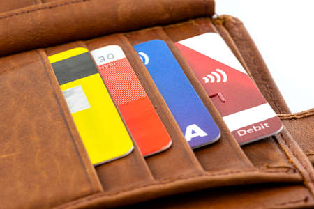 Macro photo of a brown mens leather wallet with debit and credit cards inside, isolated on a white background.