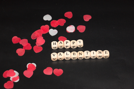 Happy Valentine written with withe cubes with black letters in front of red and white hearts on a black background