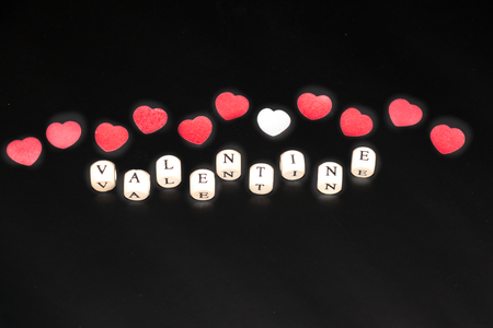 Happy Valentine written with withe cubes with black letters in front of a row of red and white hearts on a black background Stock Photo