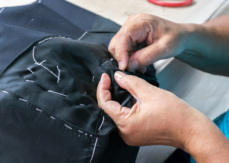 needlewoman: sewing suits , tailoring by hand Stock Photo