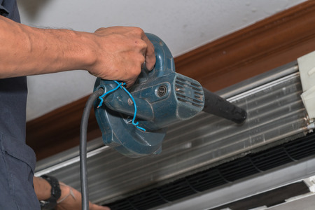 technolgy: Man use blower cleaning air conditioner