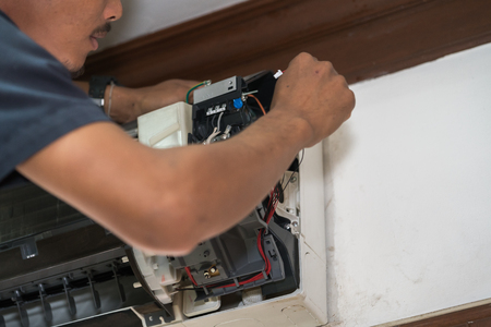 technician is fixing air conditioner