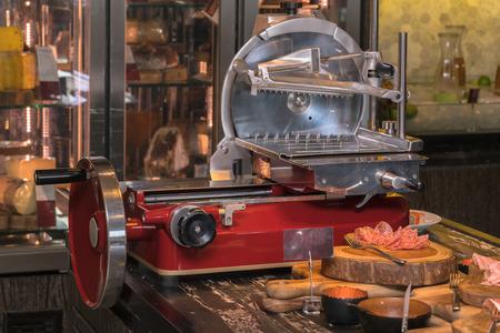 Ham slicer and fresh ham slice. Фото со стока
