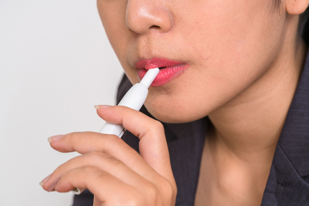 Smoker smoking hybrid smokeless cigarette device that uses real tobacco refills, a hybrid technology between analog and electronic cigarettes. Stock Photo