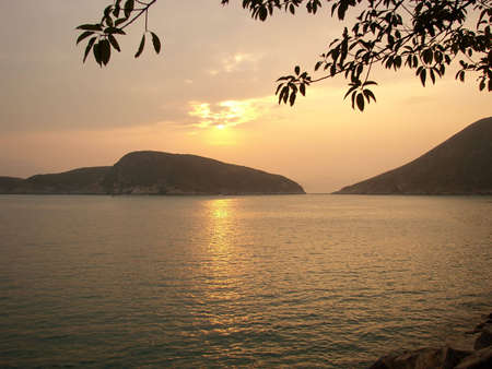 relaxing scene of sunst behind mountains in a lake photo