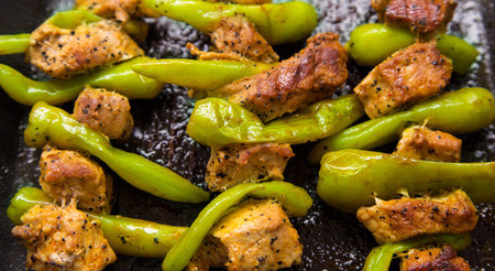barbecuing: Barbecuing pork meat with peppers.