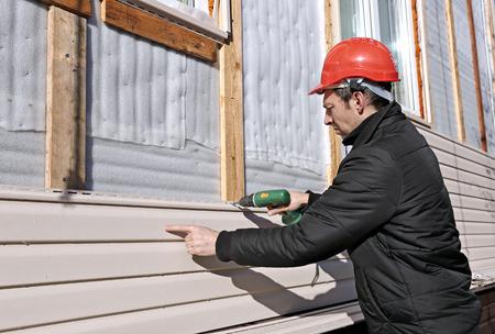 작업자가 집 외관에 패널 베이지 사이딩 설치 스톡 콘텐츠