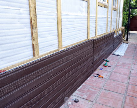 soffit cladding: Installation of brown plastic siding on the facade of the house
