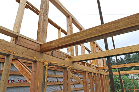 joists: Installation of wooden beams at construction the roof truss system of the frame house