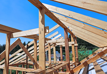 roofing system: Installation of wooden beams at construction the roof truss system of the frame house