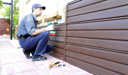 Worker installs plastic siding on the facade of the house Stock Photo - 50102353