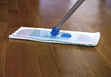 mujer limpiando: La fregona en el suelo de parquet durante la limpieza